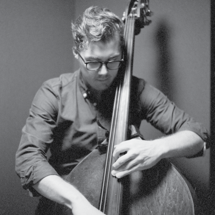 Black and white image of Alexander Svensen looking down as he plays the bass.