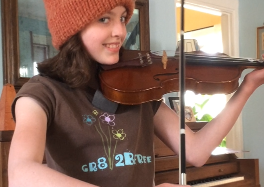 Young girl, Ella Thompson Rose playing the violin as she smiles into the camera, wearing a burnt orange knit hat and a piano in the background.