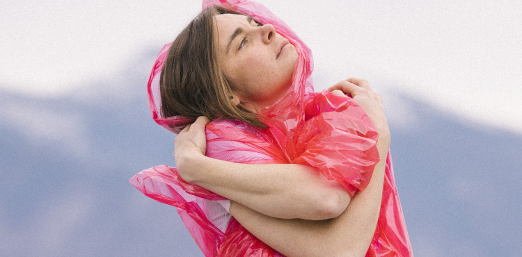 photo of Francesca Blanchard standing with her arms crossed looking up to the right. She is wearing a pink rain poncho and mountains blurry in the background.
